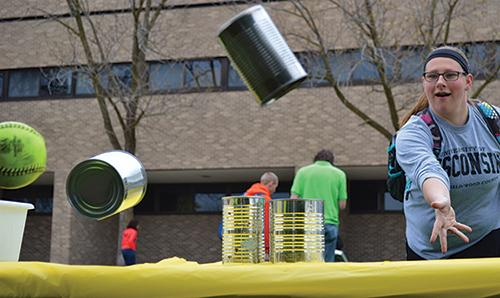 Amanda Becher senior industrial technology management major plays Can Knock-Down at the Earth Day carnival.
