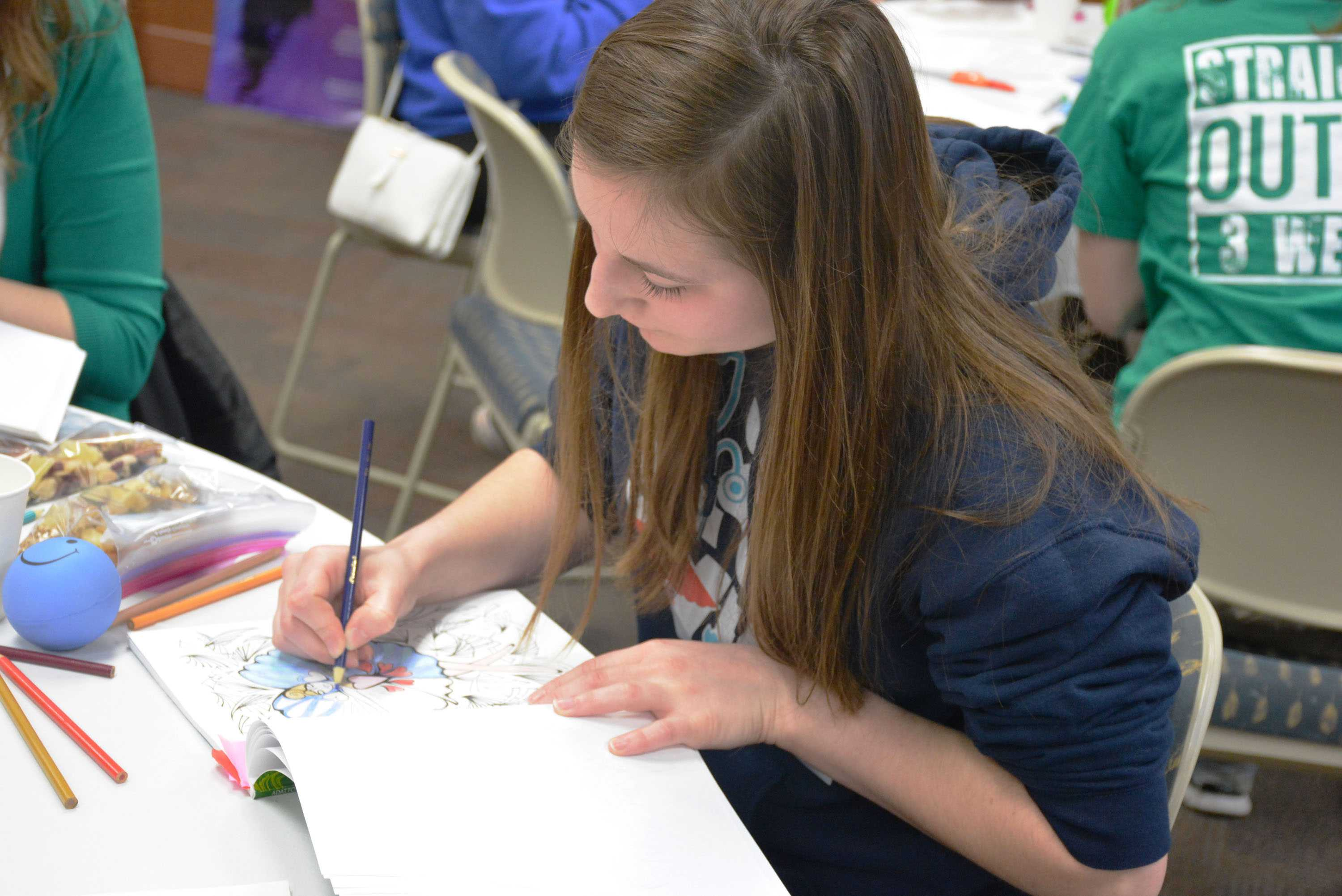 Sophomore animal science major Stephanie Frey colors in an adult coloring  book to help relax.