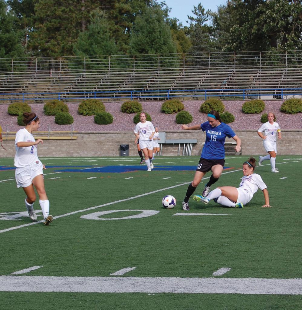 Pioneer senior defender Breanna Waldron (2) slide-tackles Aurora University's Kristina Umlauf in the first half of the Pioneers' 2-0 loss Sept. 14. The Pioneers have had solid defense thus far in 2013, but the offense has struggled.