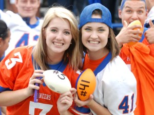 Molly Pearce (left) and Mary Ebeling were chosen to play the Ubersox drive half-time game. They had to throw miniature footballs into the bed of a truck to win a free vehicle detail service.