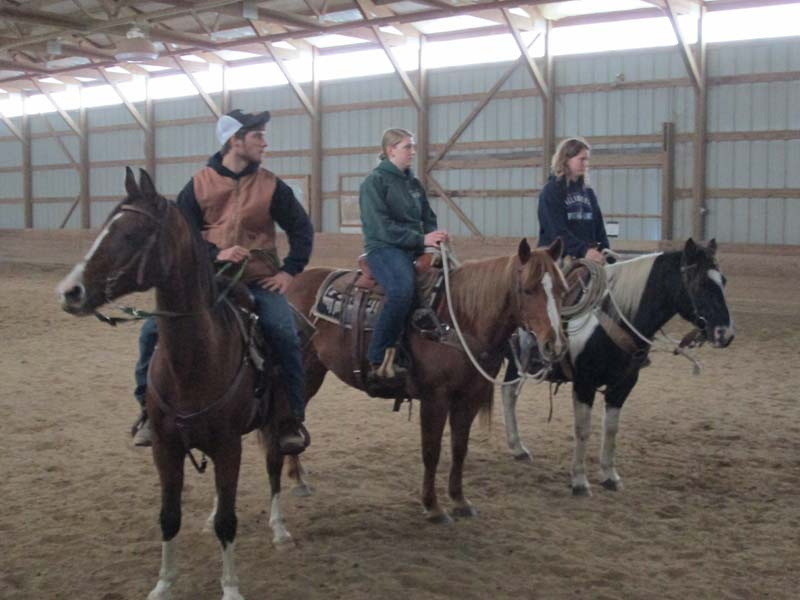 From left to right: Seniors Kyle Klotz, Jenny Raboine and Natalie Jozik listen to instructions at the Southwest Equestrian Center on Nov. 1. The Equestrian Club officially became a team this year.