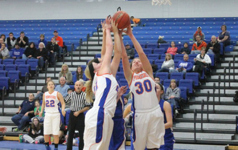 Pioneer junior forwards Alyssa Krajco (30) and Stacy Clark (21) contest for a rebound in an 81-77 overtime victory against Marian Nov. 22 Krajco and Clark are first and second, respectively, on the Pioneers in points and rebounds.