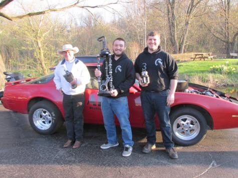 Carl Peterson, Grant Parry and Eric Kulas hold up their hand-made trophies from the Best in Show contest in front of AEC's 1985 Pontiac Firebird club car.  The trophies were created by AEC members who welded old, broken car parts together at their shop.