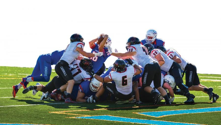 Quarterback Tom Kelly dives over the pile for the overtime score which led to a Pioneer 35-28 victory over North Central.