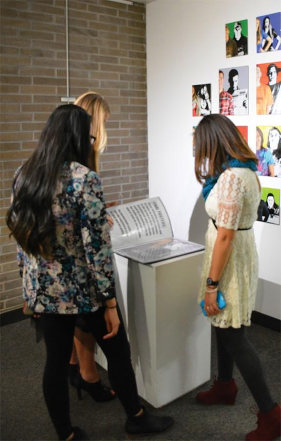 Media studies major Mathea Durica, business administration major Hannah Shuler and senior graphic design major Carley Rote observe Shuler's work at the opening of the Array 15 Exhibit.