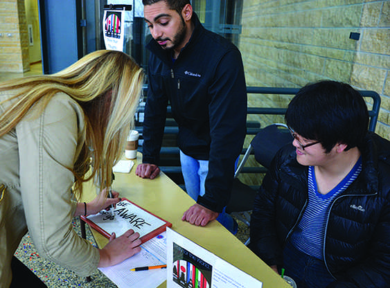 Junior business administration major Sierra Hartman , sophomore computer science major Mohammad AL Shatti  and engineering major Ryan Kim show support for international students and global victims of terrorism.