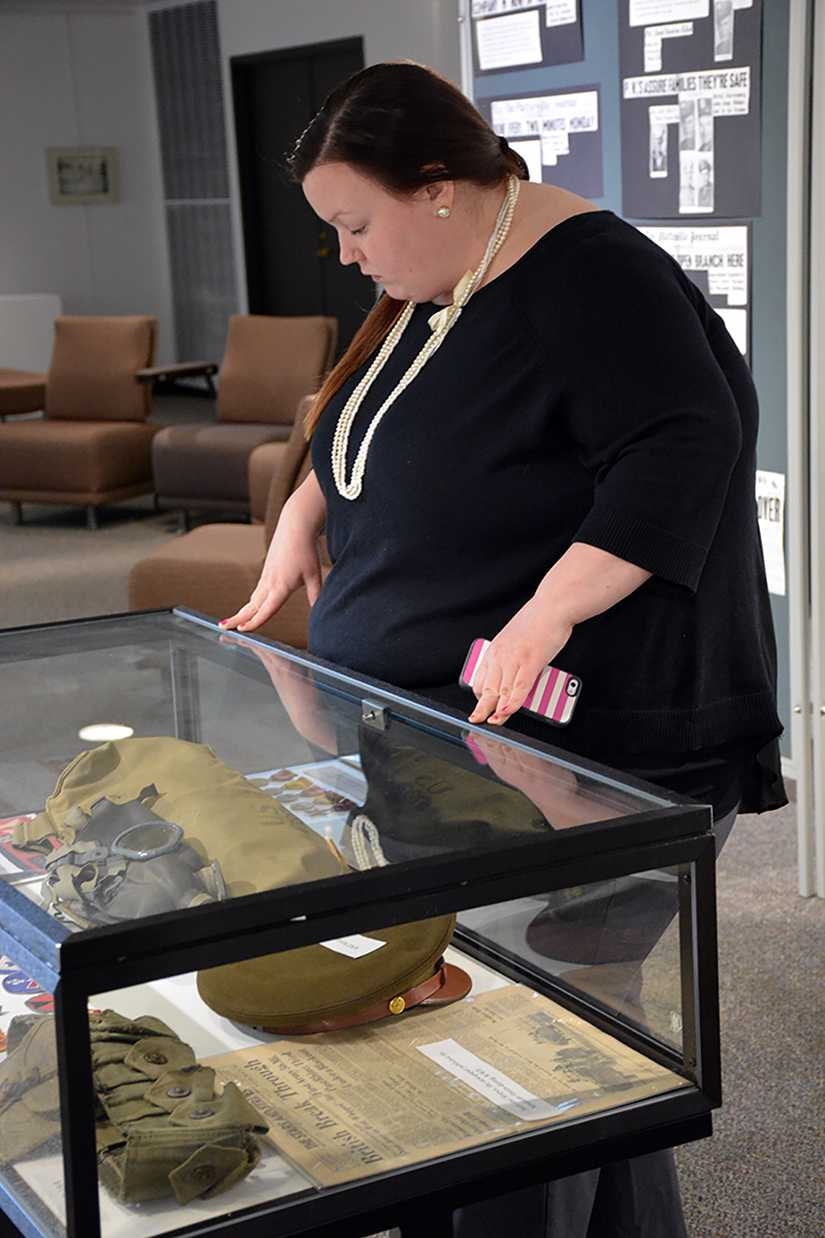 Jodi Moen, counselor at University Counseling Services, looks at a case of military artifacts including historic apparel.