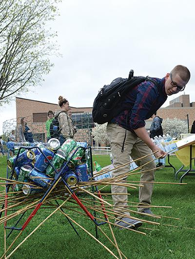 Taylor Rucks sophomore computer science major participates in a game at the Earth Day carnival that involved sticks and cans which was the carnival's rendition of the game KerPlunk