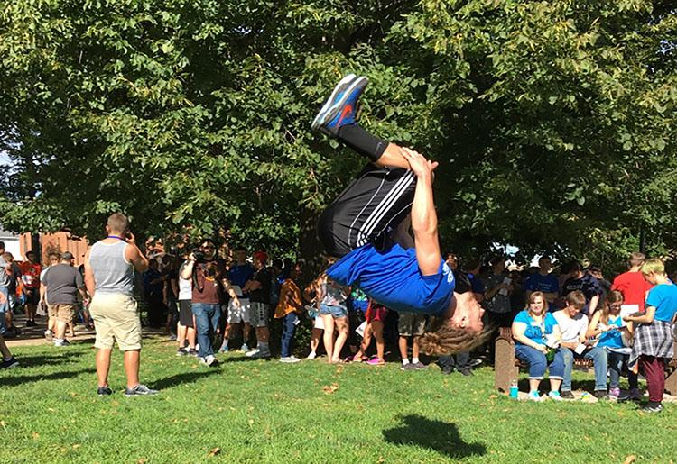Senior male cheerleader Aaron Bakkila shows off his tumbling skills in City Park during UW-Platteville's welcome weekend. Here he is shown throwing a back tuck.