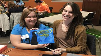 Senior business administration and industrial technology major Jocelyn Key and senior biochemistry and biology major Mallory Jasicki show-off their artwork at Paint and Punch.