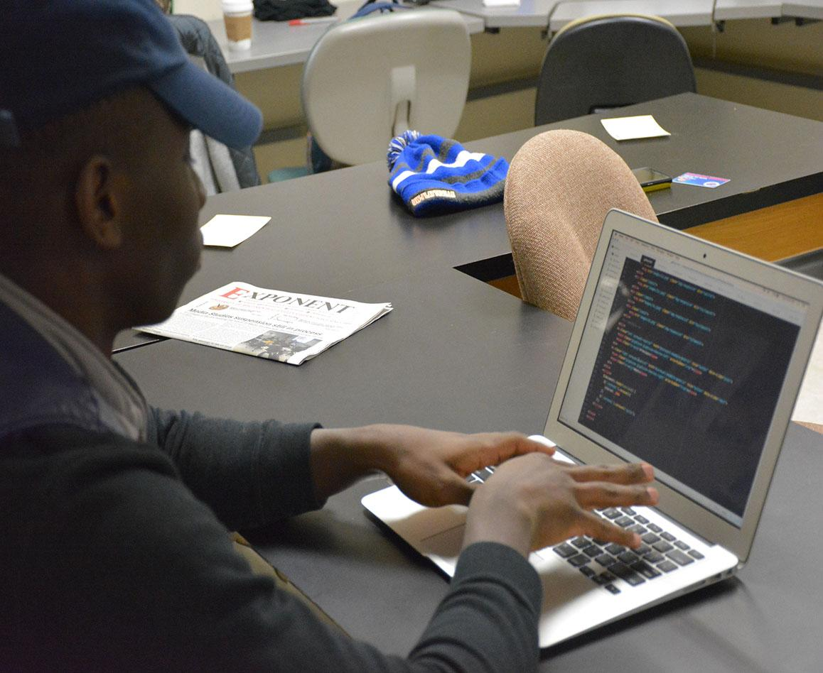 Senior media studies major Muhammed Umar works on HTML coding.