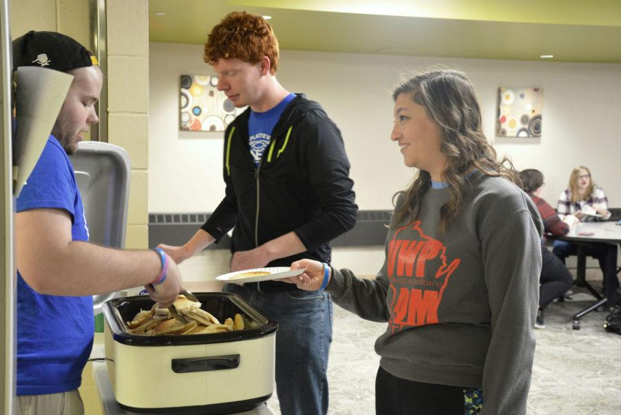 Senior building construction major and Morrow Hall Resident Assistant Jake Schaap helps his resident building to serve pancakes to senior education majors Lukas Wymer and Hayley Pollei. Students were incouraged to wear flannel while eating flapjacks during the Friday Night Club event.