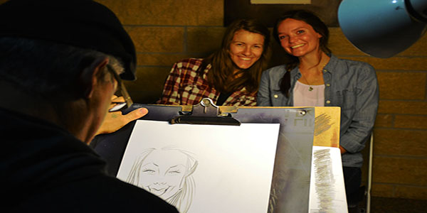 Junior mechanical engineering majors Elisa Broughton and Beth Klein pose for a photo while getting their faces drawn by a charicature artist.