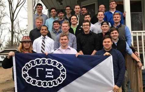 Sigma Tau Gamma members pose together with their fraternity's flag to show their brotherhood.