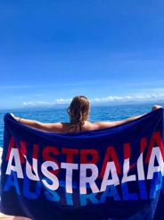 Senior animal science major Jessie Thompson poses with an Australian banner as she over looks the ocean during her study abroad experience.