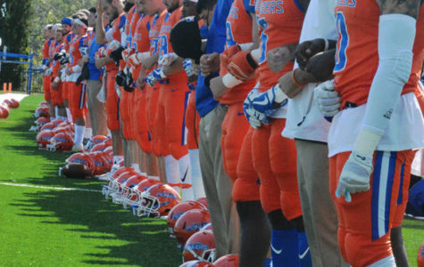 The University of Wisconsin-Platteville football team stands together with locked arms during the national anthem.